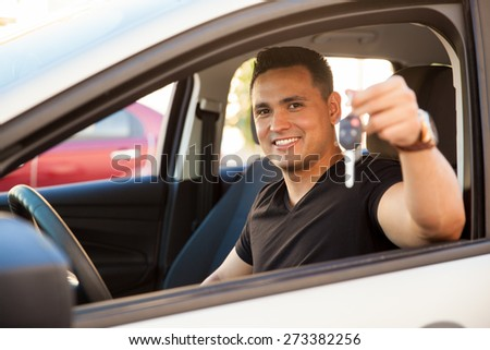 Attractive young Hispanic man showing his new car keys and smiling - stock photo