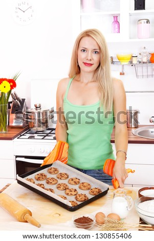 Attractive young housewife with freshly baked chocolate cookies in the kitchen