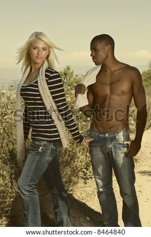 attractive young interracial couple standing in a desert field - stock photo