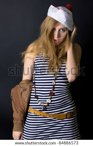 Attractive young lady in sailor dress and hat in studio on the black background - stock photo