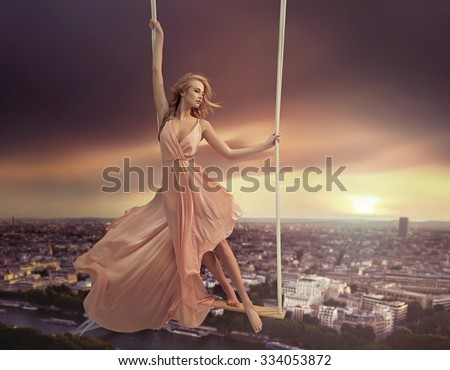 Attractive young lady on a swing above the city - stock photo