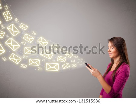 attractive young lady standing and holding a phone with message icons - stock photo