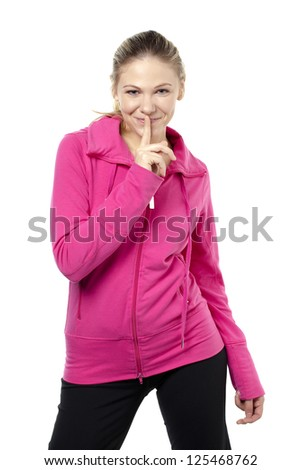 Attractive young lady with fingers on her lips over a white background - stock photo