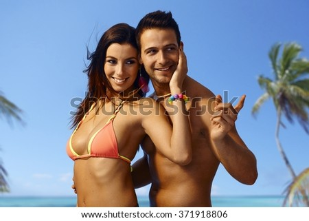 Attractive young loving couple embracing on the beach at summer holiday, smiling. - stock photo
