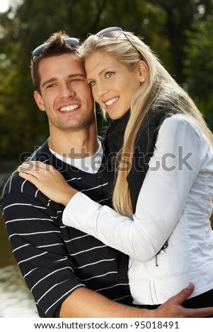 Attractive young loving couple hugging in park, smiling.? - stock photo