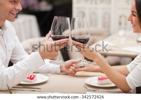 Attractive young loving couple is dating and flirting in cafe. They are sitting at the table and holding hands. The lovers are looking at each other with love and smiling. They are drinking wine - stock photo