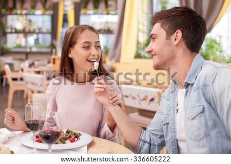 Attractive young loving couple is dating in restaurant. They are eating salad and drinking wine. The man is feeding woman with tasty food. They are looking at each other and smiling - stock photo