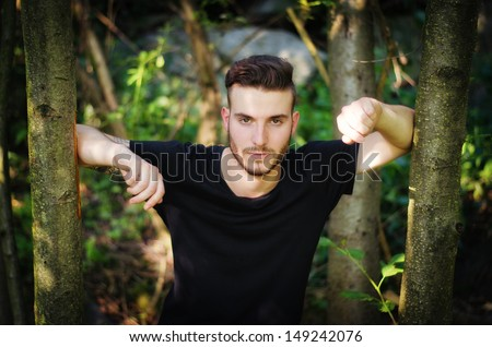 Attractive young man among green trees, plants and leaves - stock photo