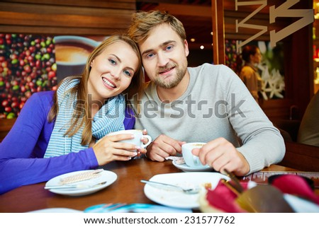 Attractive young man and his girlfriend having coffee in cafe - stock photo