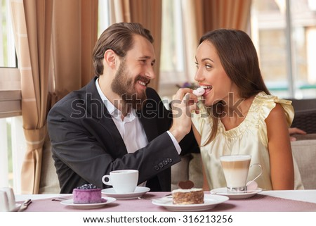 Attractive young man and woman are dating in cafe. They are sitting at the table and smiling. The man is feeding his girlfriend with sweet dessert. They are enjoying hot drinks - stock photo