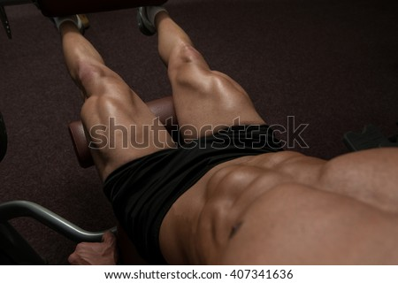 Attractive Young Man Doing Leg Exercises With Machine In Gym - stock photo