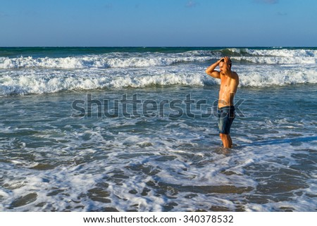 Attractive young man enjoys splashing in the ocean water, in the summer at dusk.