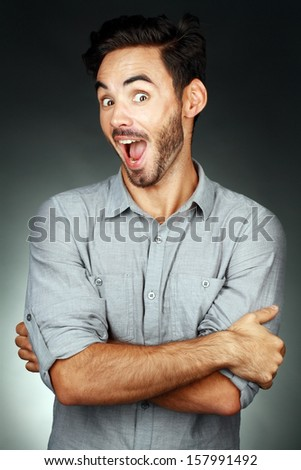 attractive young man exited and amazing looking at camera and making face - stock photo