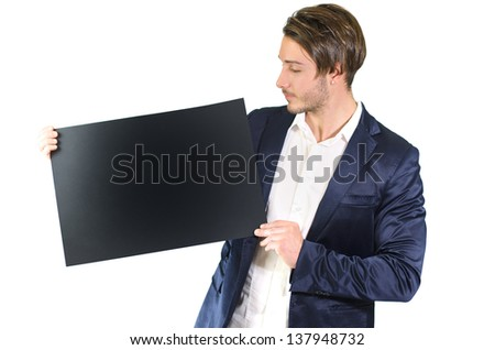 Attractive young man holding and showing empty, blank black board, sign or paper sheet