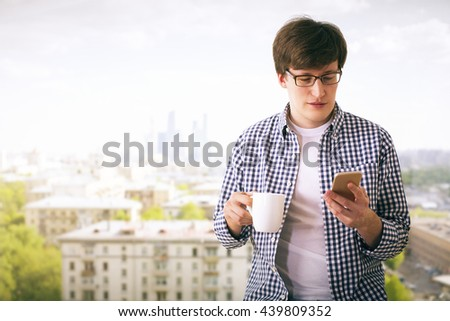 Attractive young man holding coffee cup and using mobile phone on city background - stock photo