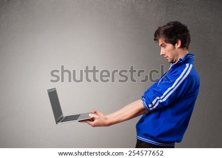 Attractive young man holding modern notebook - stock photo