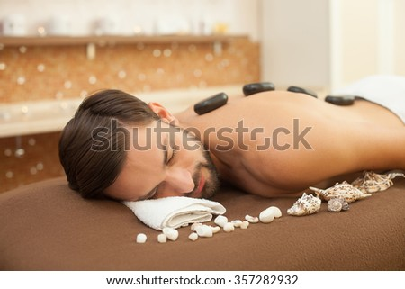 Attractive young man is getting stone massage at spa. He is lying near the mussels and relaxing. His eyes are closed with pleasure - stock photo
