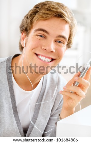Attractive young man is listening to music at home using mobile
