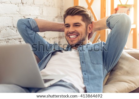 Attractive young man is using a laptop and smiling while lying with hands behind head on sofa at home - stock photo