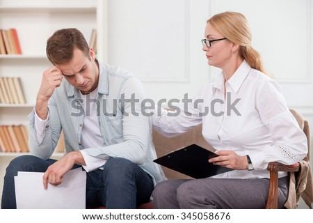 Attractive young man is visiting psychologist. He is crying with stress and holding papers. The woman is sitting near him on sofa. She is touching his back and trying to calm him down - stock photo