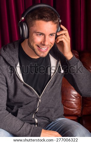 Attractive young man listening to headphones - stock photo