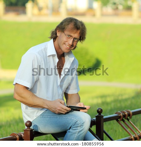 attractive young man looking into a tablet - stock photo