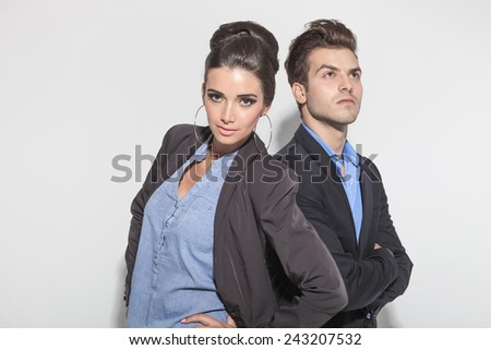 Attractive young man looking up with his arms crossed while his girlfriend is posing with her hands on her hips. - stock photo