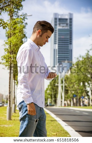 Attractive young man outdoor wearing white shirt in city, checking the time by looking at wrist watch