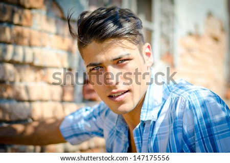 Attractive young man outdoors smiling and looking in camera, blue shirt, in front of brick wall - stock photo