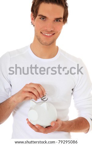 Attractive young man puts Euro symbol in piggy bank. All on white background. - stock photo
