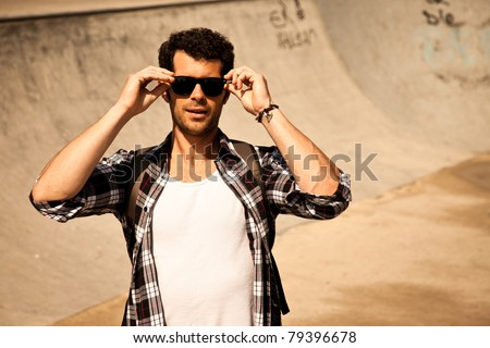 Attractive young man putting on his sunglasses. - stock photo
