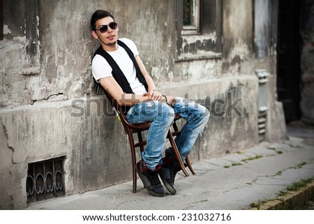 Attractive young man relaxing in urban background - stock photo