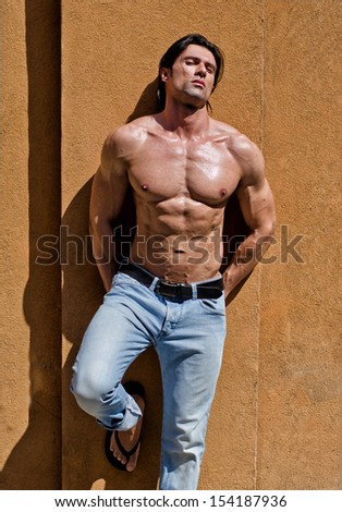 Attractive young man shirtless with jeans leaning against a wall with his eyes closed - stock photo