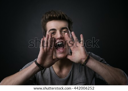Attractive young man shouting out loud with hands around mouth