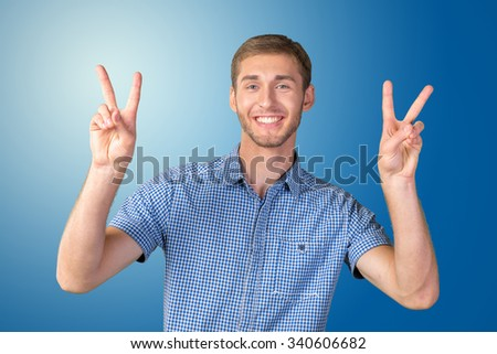 Attractive young man shows a sign of peace or victory - stock photo