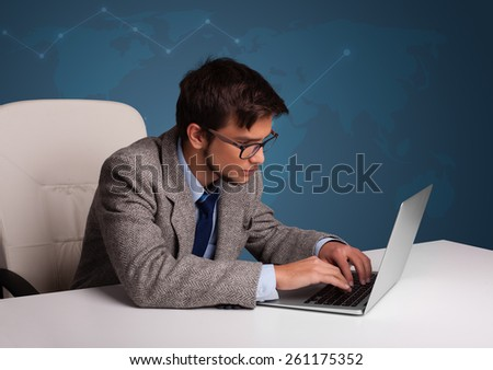 Attractive young man sitting at desk and typing on laptop