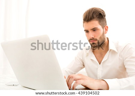 Attractive young man sitting at the table with a laptop computer.