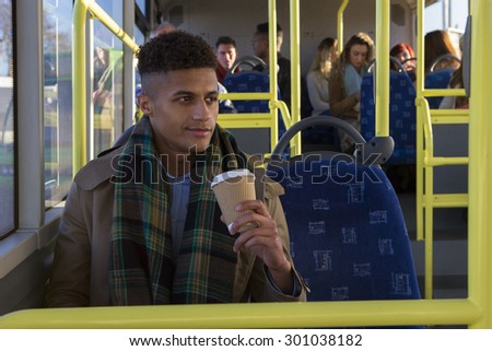 Attractive young man sitting on the bus with a cup of coffee. He is looking out the window and is smiling. - stock photo
