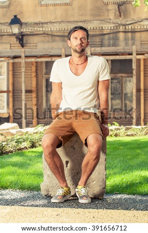 Attractive young man sitting outside on a rock stone and wearing modern casual clothes - stock photo