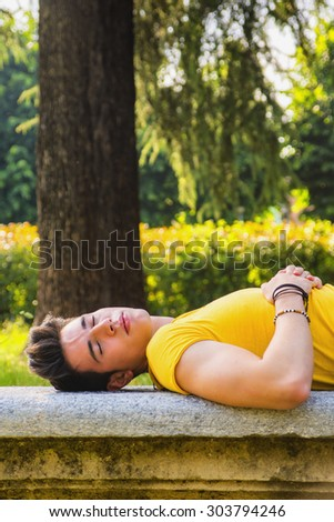 Attractive young man sleeping on stone bench outdoor in city park during day - stock photo