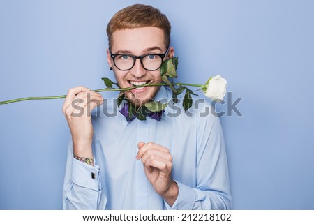 Attractive young man smiling with a white rose in his mouth. Date, birthday, Valentine. Studio portrait over blue background - stock photo