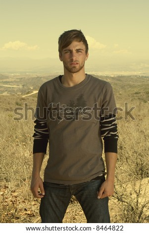 attractive young man standing in a desert field - stock photo