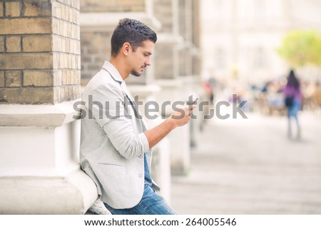 Attractive young man using mobile phone while relaxing in the city - stock photo