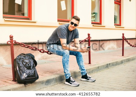 Attractive young man using mobile phone while relaxing in the city, bag and a lion, sunglasses, shoes, jeans, cap, boy laughs, Hipster style guy - stock photo