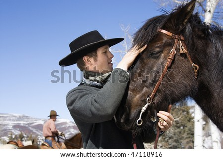 Attractive young man wearing a cowboy hat. He is petting a horse with another rider in the background. Horizontal shot. - stock photo