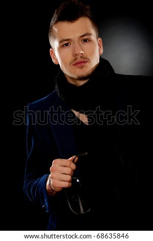 attractive young man wearing elegant blue suit and holding sunglasses in his hand - stock photo
