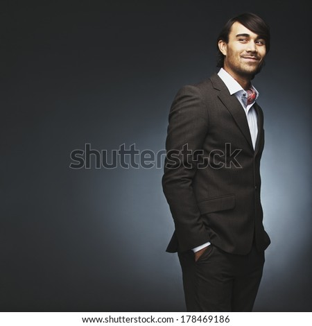 Attractive young man wearing suit standing with his hands in pocket looking over shoulder. Handsome male fashion model posing on black background with lots of copyspace. - stock photo
