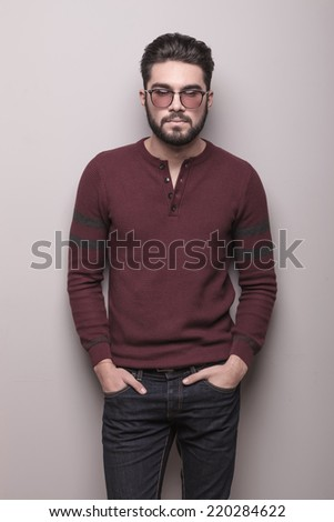 Attractive young man wearing sunglasses and a burgundy sweater, holding his hands in pocke, lookint at the camera