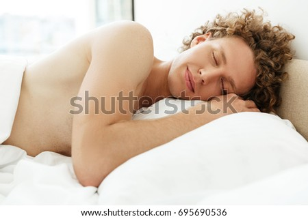 Attractive young man with curly hair sleeping in bed at home