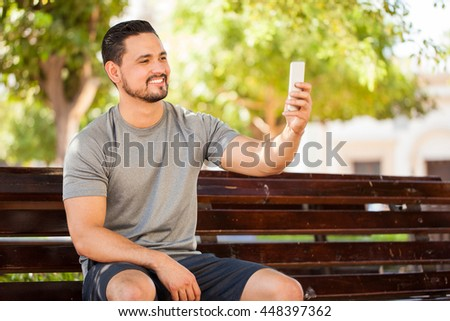 Attractive young man with sporty outfit taking a selfie while sitting in a park bench before exercising outdoors - stock photo